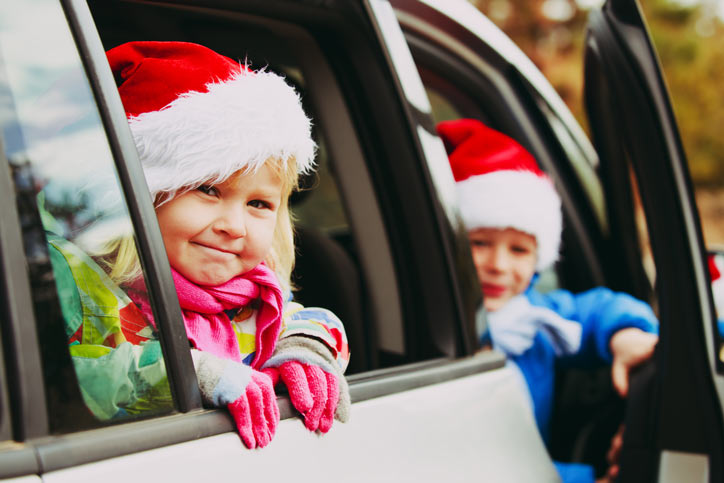 Children wearing Santa hats in a car